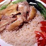 A plate of chicken rice topped with chicken wings and vegetables. Brought to Singapore by the people of Hainan, an island off the southern-coast of China, this is a national dish loved by Singaporeans.