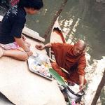 A layperson offers food and flowers to a passing monk.
