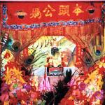 An inner shrine may contain a few figures of ancient Chinese men (ancestor worship), a garuda figurine (Hinduism), a yin-yang (dualism), and an amulet containing a miniature monk statue (Buddhism). It may also contain a host of other objects whose religious significance is unclear or nil (joss sticks, garlanded elephant statues, tiger paintings, peacock feathers, potted plants.) The result often resembles a stall at a flea market, or a garish and dusty curio store in some Chinatown.
