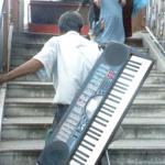 A blind keyboard player lugs his instrument up the stairs.